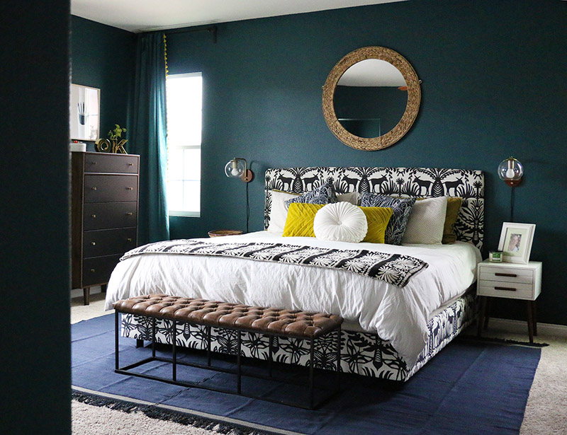 dark teal bedroom with black and white bed