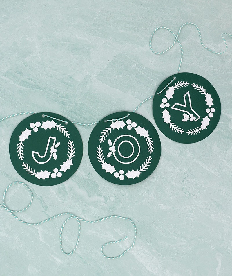 diy paper joy banner made using dark green cardstock, white glitter heat transfer vinyl, and free winter monogram cut files