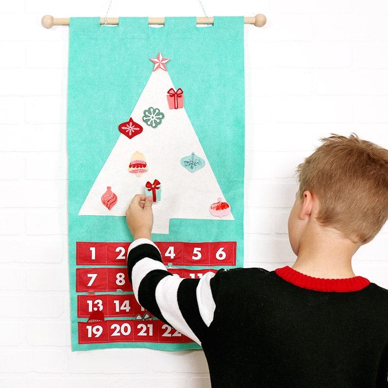 child putting ornament on DIY felt Christmas tree advent calendar