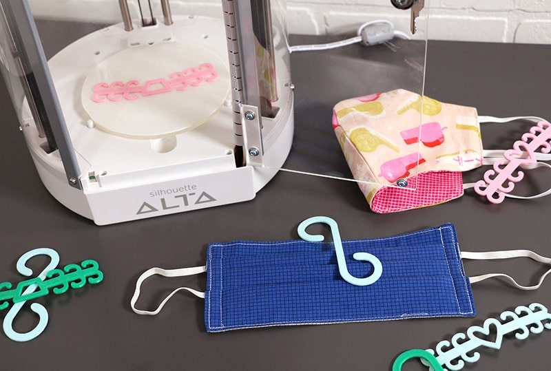finished 3d printed ear savers pictured with cloth face masks and silhouette alta 3d printer