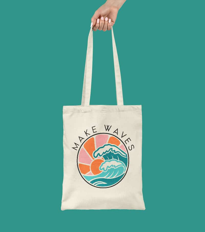 hand holding canvas tote bag decorated with multi-color make waves ocean cut file design on green background