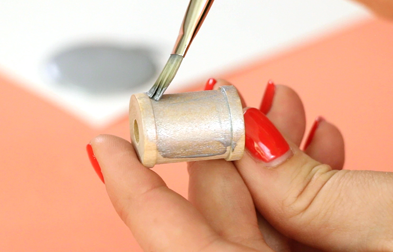 painting small wooden spool with metallic silver paint