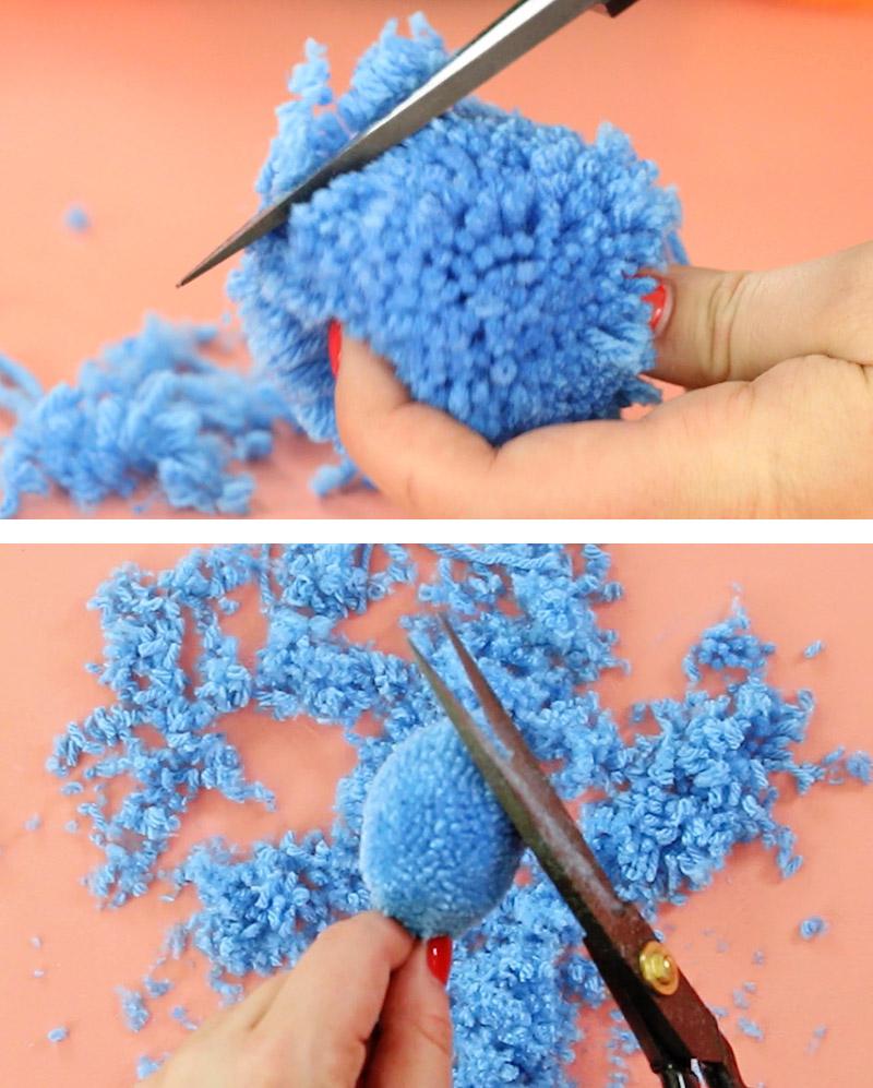 scissors trimming blue pom pom into oval shape