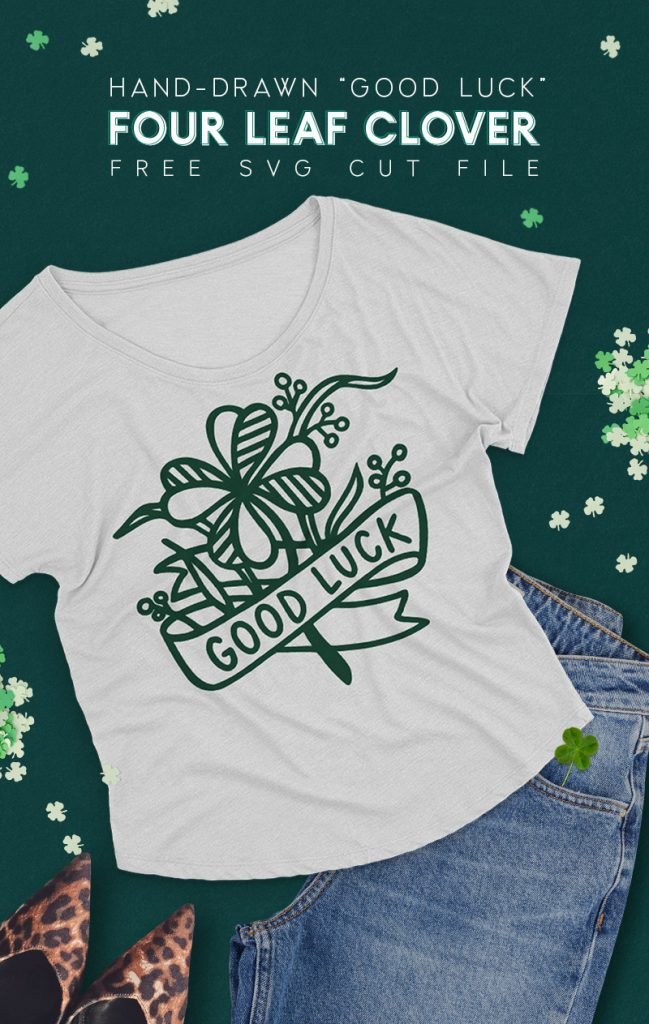 "Gray t-shirt on dark green background surrounded by jeans, leopard print shoes, and paper four leaf clover confetti. The t-shirt has a dark green design on it depicting a hand drawn four leaf clover with a ribbon banner that reads ""good luck."""