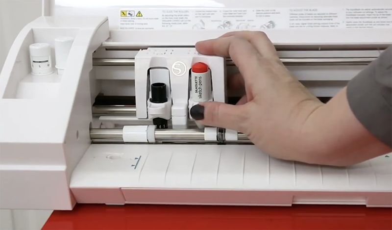 Hand putting a red Silhouette sketch pen into the second tool holder of a Silhouette Cameo 3.