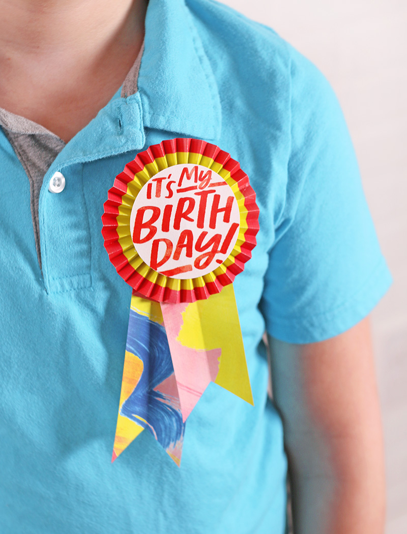 Child wearing light blue polo shirt with paper rosette button pinned on shirt. Button reads it's my birthday!